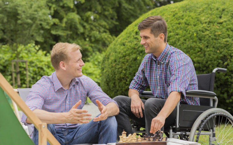 Shot of two friends playing chess in a park