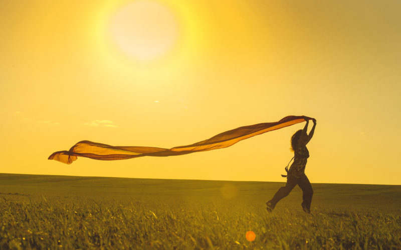 Young woman running on a rural road at sunset in summer field. Lifestyle freedom sports background. Happiness concept.