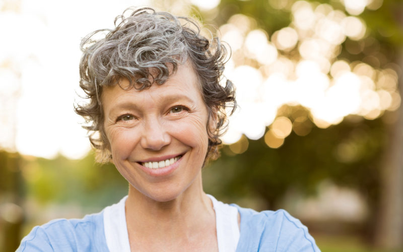 Portrait of senior woman relaxing at park. Close up face of happy senior woman looking at camera. Portrait of a smiling mature woman with grey hair.