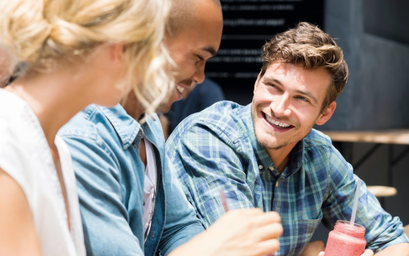 Group of friends in a cafe relaxing outdoor. Portrait of young man drinking smoothie while chatting with friends at sidewalk cafe. Group of smiling guys and happy girl meeting at outdoor coffee shop.