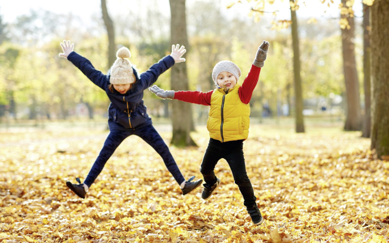 childhood, season and people concept - happy children running on fallen leaves at autumn park