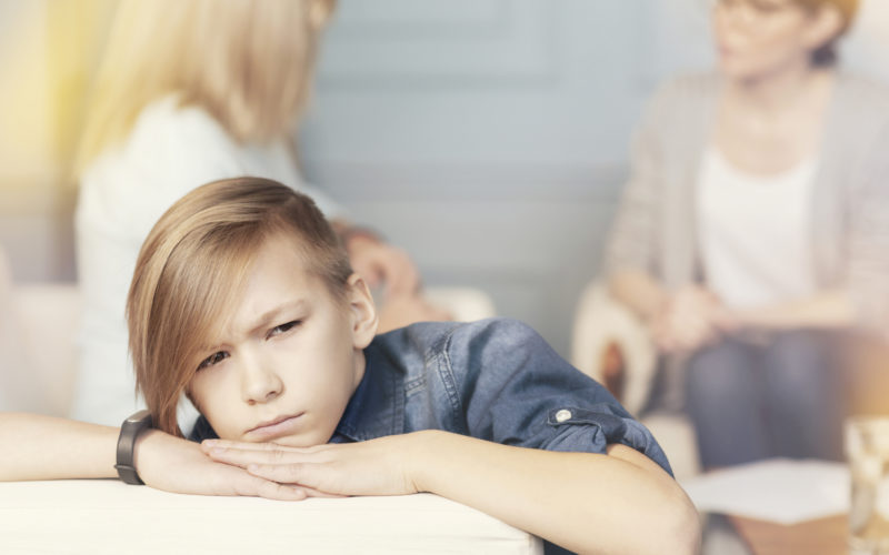 Feeling sad. Close up of a depressed teenager boy sitting on the sofa while a professional female psychologist and concerned mother talking in the background